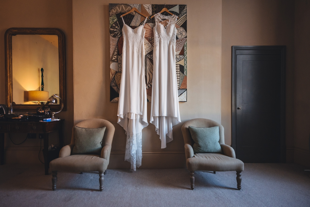 Symmetrical image of two brides dresses beside two chairs