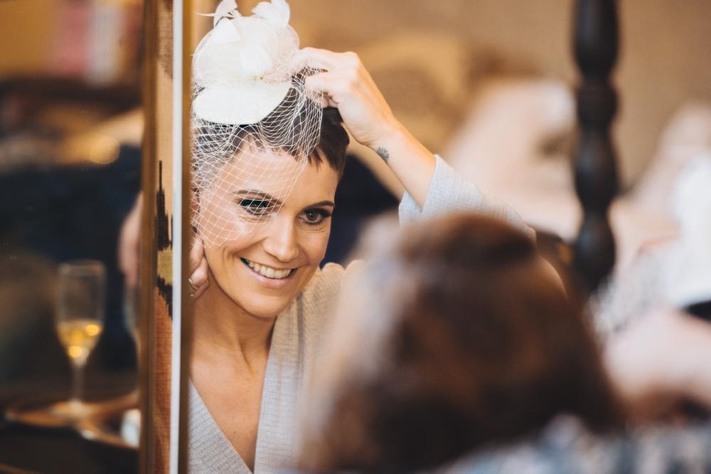Bride looking in mirror adjusting veil