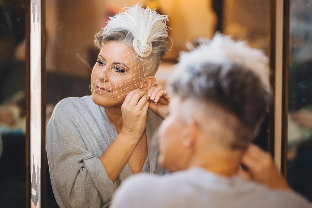 Bride looking in mirror putting in earrings