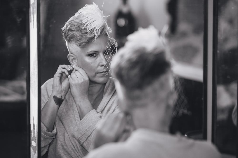 Black and white image of bride adjusting earrings