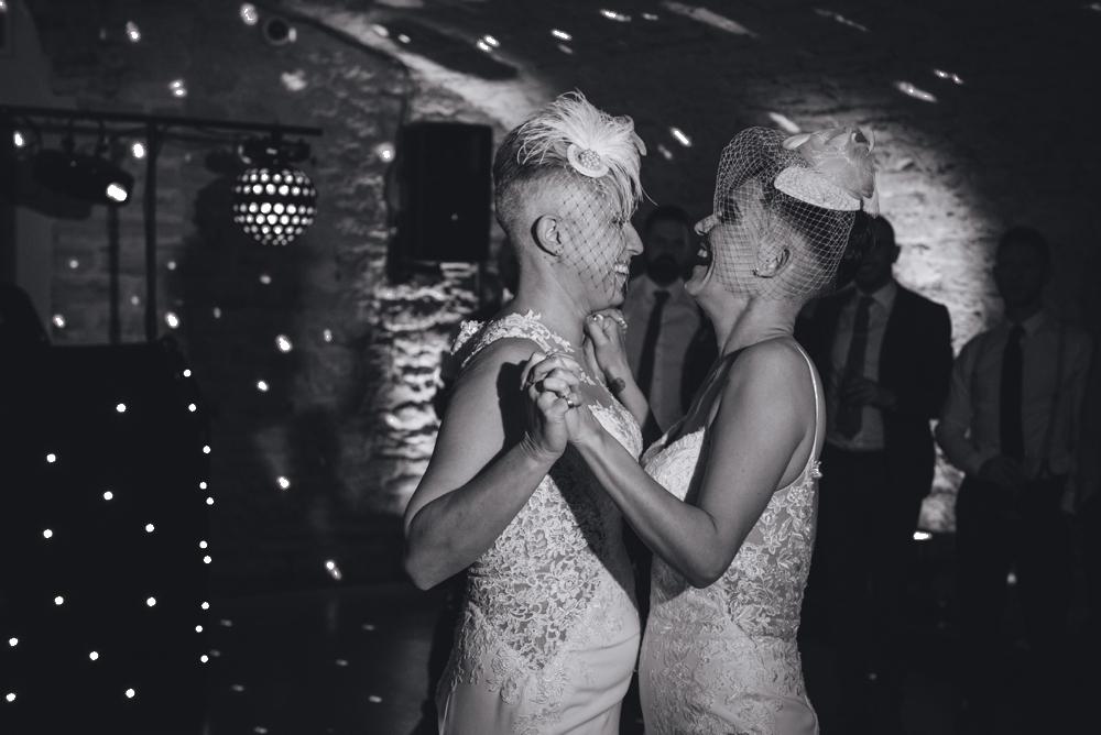 Black and white image same sex wedding couple on dance floor