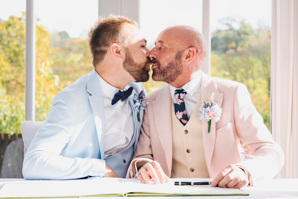 Signing the wedding register. Same sex male couple