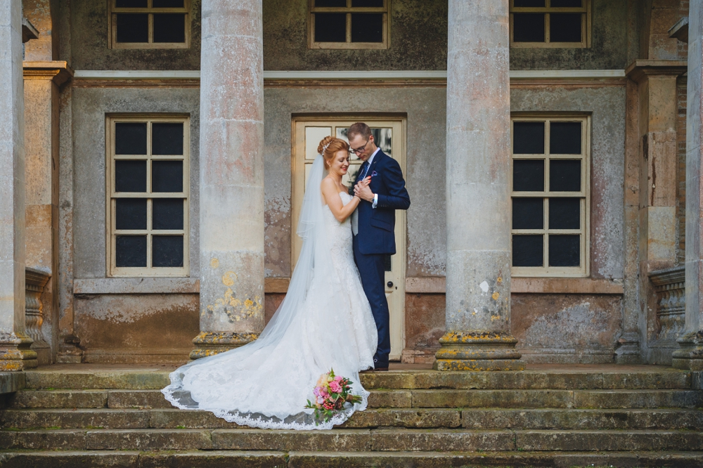 Bride and groom on steps of Holkham Hall. Formal portrait