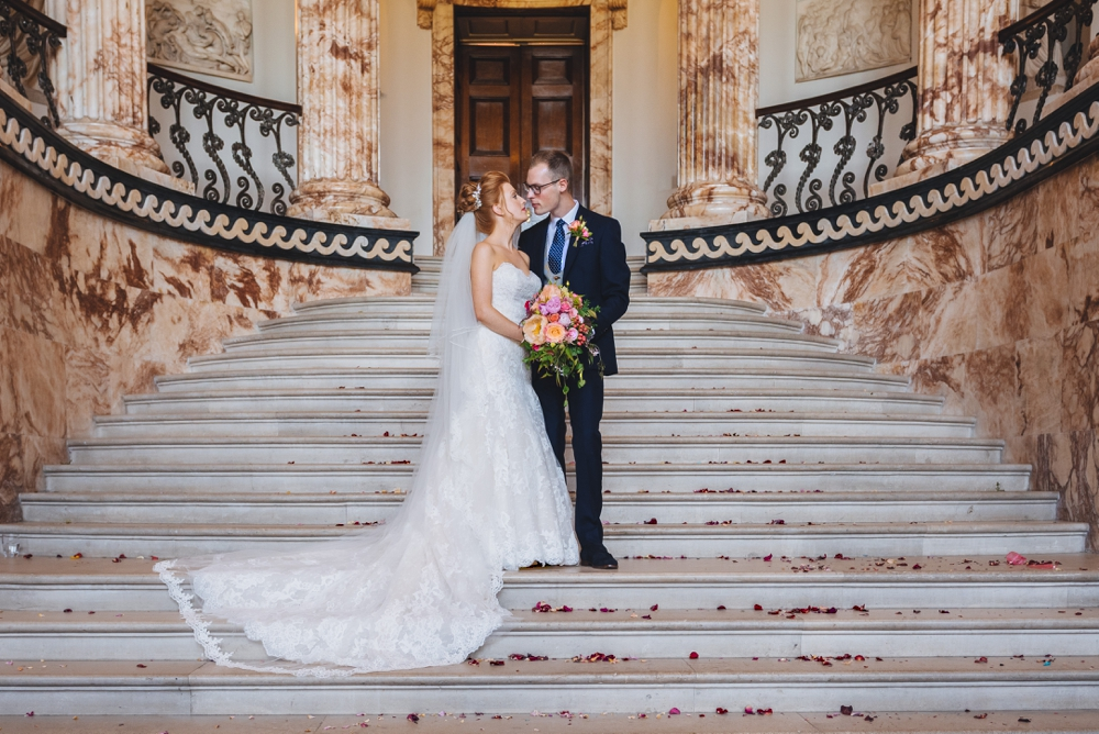 Bride and Groom standing on the steps in the marble hall at Holkham Hall Norfolk