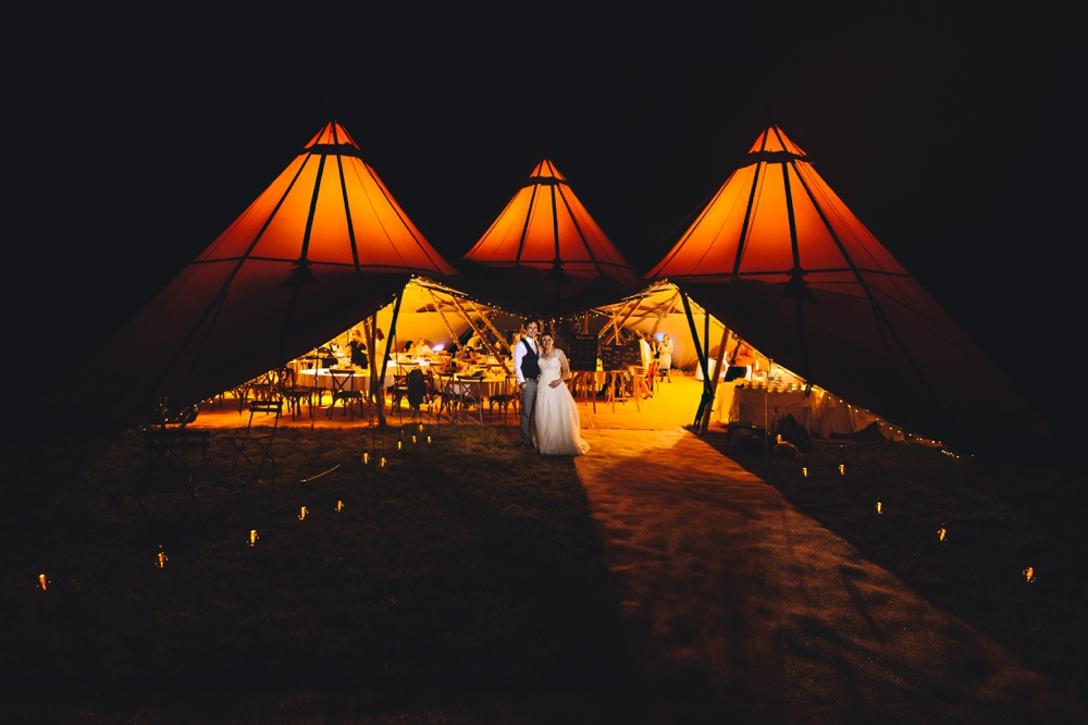 Cottenham Racecourse Bride and Groom standing outside Tipi wedding marquee