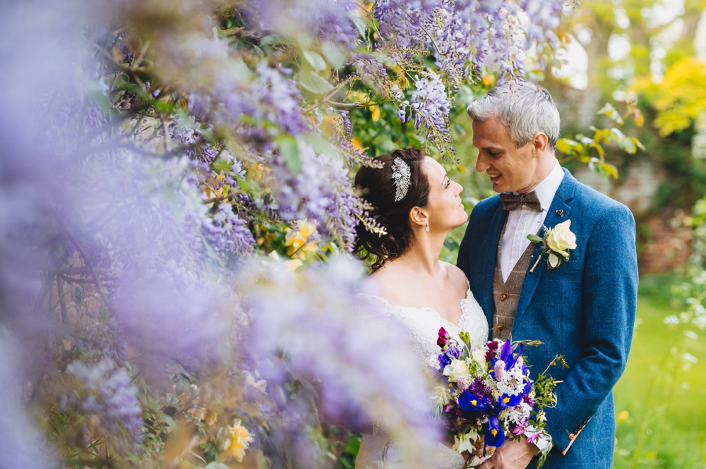 Bride and Groom against lilac wisteria Preston Court Canterbury