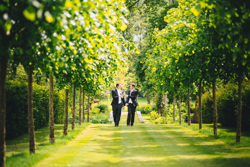 Same sex Grooms walking between avenue of trees Oxnead Hall Norfolk