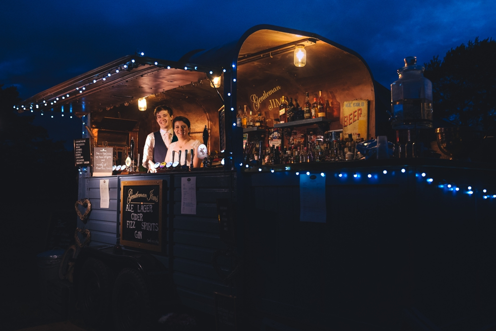 Bride and Groom standing inside mobile horse box bar on wedding day