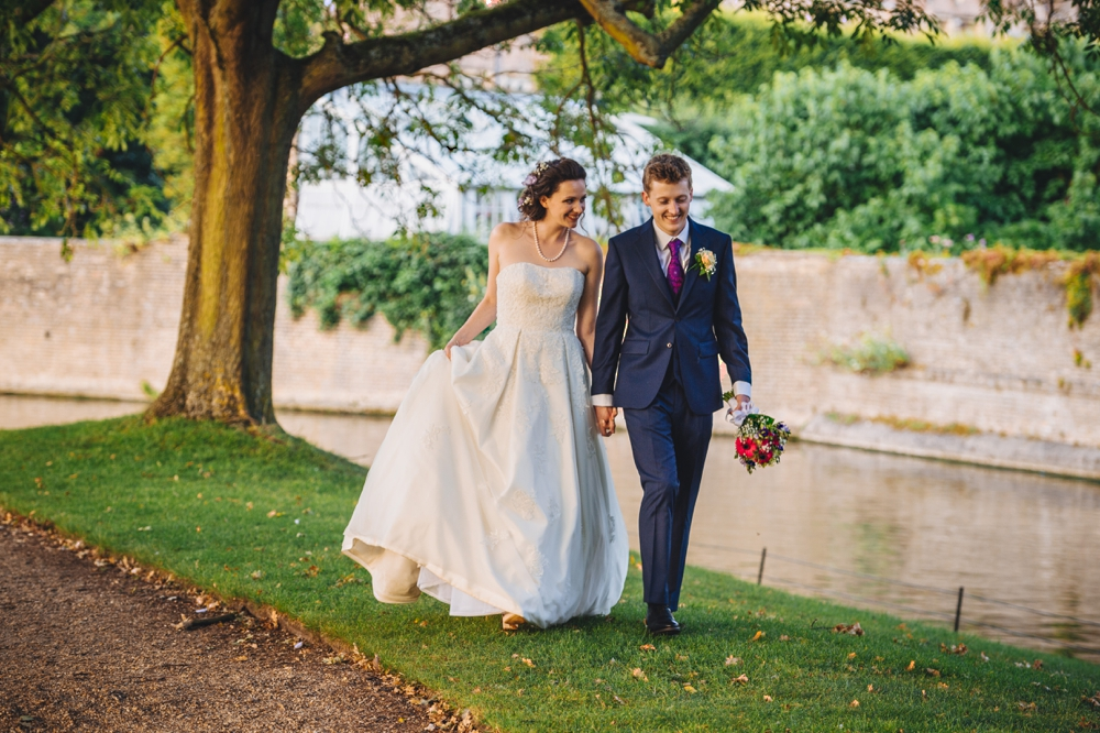 Bride and Groom walking through the gardens St Johnes College Cambridge