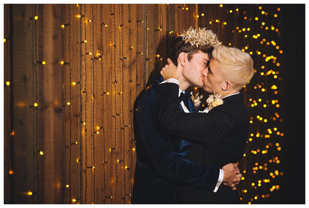 Grooms kissing against star light curtain