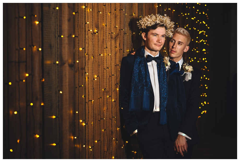 Two grooms standing in front of star light curtain