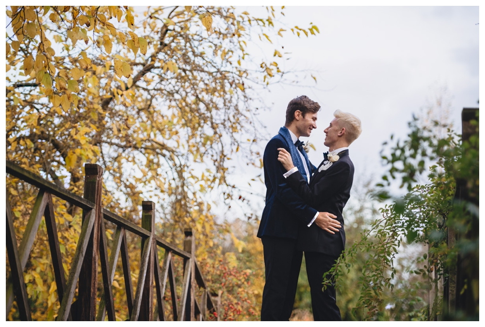 Male couples standing on bridge at Oxnead Hall